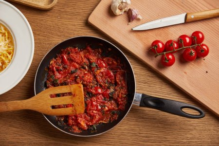 top view of frying pan with tomato sauce for pasta on wooden table