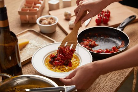 cropped shot of woman putting tomatoes from frying pan onto spaghetti in plate