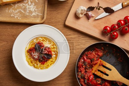 Photo for Top view of plate of pasta and frying pan of tomato sauce on wooden table - Royalty Free Image