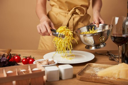 cropped shot of woman in apron putting spaghetti on plate from colander