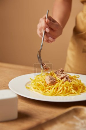 cropped shot of woman putting chicken meat onto spaghetti in plate