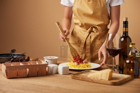 cropped shot of woman in apron putting sauce onto pasta in plate on wooden table