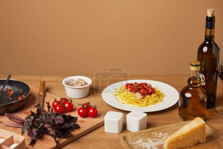 plate of pasta with various ingredients and wine around on wooden table