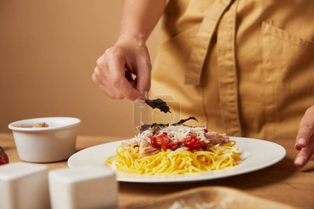 cropped shot of woman in apron decorating pasta with basil leaves