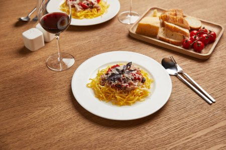 close-up shot of plates of spaghetti with red wine in glasses for romantic dinner