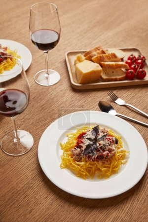 Photo for Close-up shot of plates of spaghetti with red wine in glasses on wooden table - Royalty Free Image