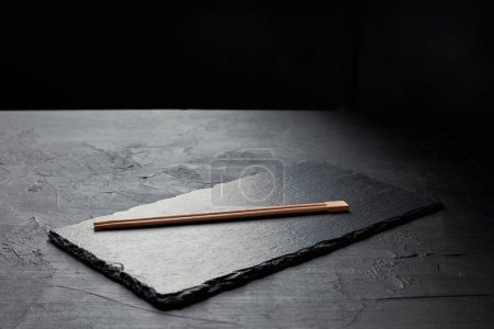 close-up view of slate board and chopsticks on black