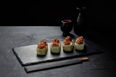 Photo for Gourmet sushi roll with creamy eel and kimchi mayonnaise on slate board and chopsticks on slate board - Royalty Free Image