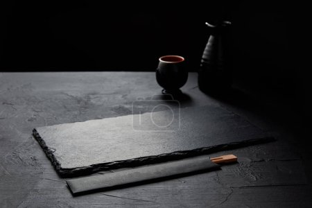 empty black slate board, chopsticks, jug and mug