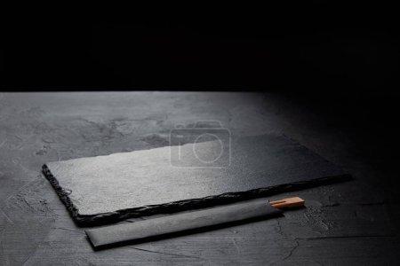 black slate board and chopsticks for eating in japanese restaurant