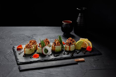 gourmet sushi roll with creamy eel and kimchi mayonnaise on slate board and chopsticks
