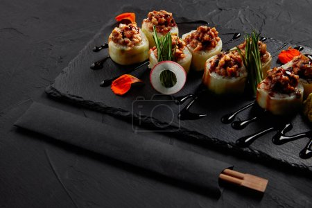 Photo for Delicious sushi roll with creamy eel and kimchi mayonnaise on slate board and chopsticks - Royalty Free Image