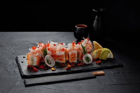 close-up view of delicious delicious roll in mamenori with shrimp, salmon and avocado on slate board