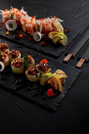 köstliche Rolle in Mamenori mit Garnelen, Lachs und Avocado in Sauce Nigiri und Rolle mit cremigem Aal und Kimchi-Mayonnaise