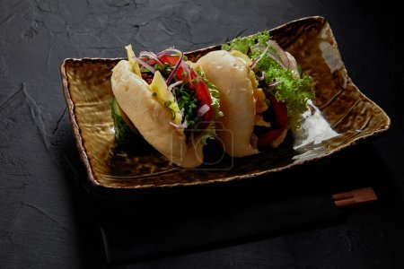 close-up view of delicious spicy pork buns with vegetables on plate