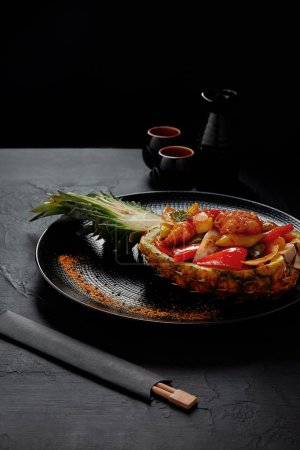 gourmet japanese dish served in halved grilled pineapple and chopsticks