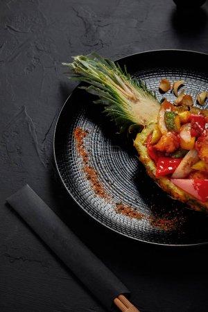vue rapprochée du délicieux plat japonais servi en baguettes et ananas coupés en deux