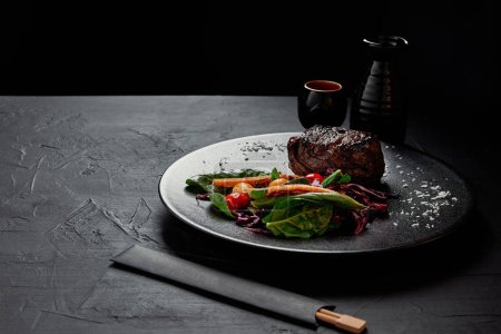 delicious beef steak in Teriyaki sauce with grilled cherry tomatoes, red cabbage and leaves of spinach, baby corn and kumquat