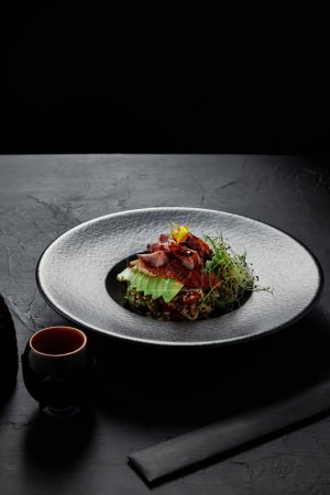 Photo for Delicious Japanese Ceviche with seafood, avocado and herbs on black plate - Royalty Free Image