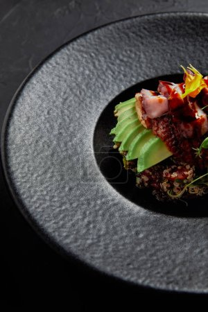 close-up view of delicious traditional japanese dish with seafood, avocado and herbs on black plate