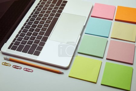 laptop, set of paper stickers, pencil and paper clips on white tabletop