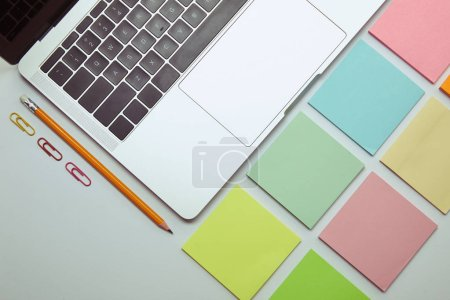 flat lay of laptop, set of colored paper stickers, pencil and paper clips on white tabletop
