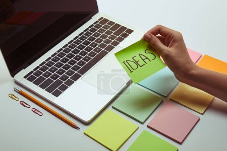 cropped image of woman holding paper sticker with word ideas near laptop