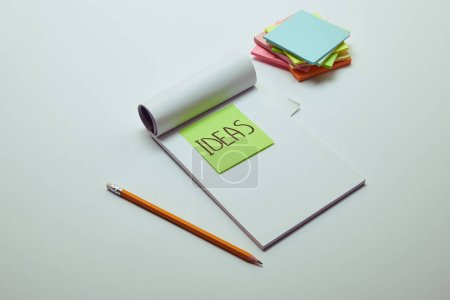 Photo for Paper sticker with word ideas in notebook, pencil and pile of note papers on white tabletop - Royalty Free Image