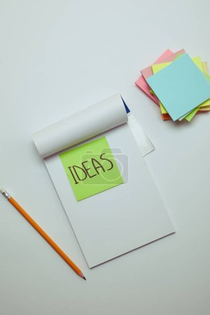 Photo for Top view of paper sticker with word ideas in notebook, pencil and pile of note papers on white tabletop - Royalty Free Image