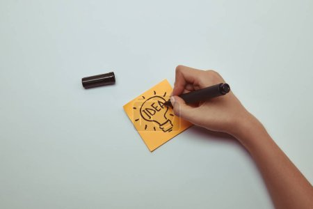 Photo for Cropped image of woman drawing word idea in lightbulb on paper sticker - Royalty Free Image