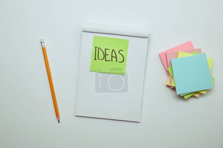 elevated view of paper sticker with word ideas in notebook, pencil and pile of note papers on white tabletop
