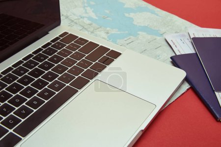 laptop, map, passports with tickets on red tabletop