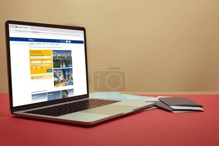 laptop with loaded booking page on table at home