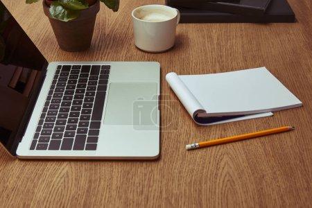 portátil, taza de café, cuaderno y lápiz en el tablero de madera