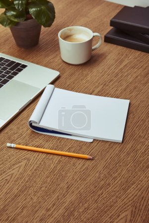 Photo for Laptop, notebook and pencil on wooden brown tabletop - Royalty Free Image