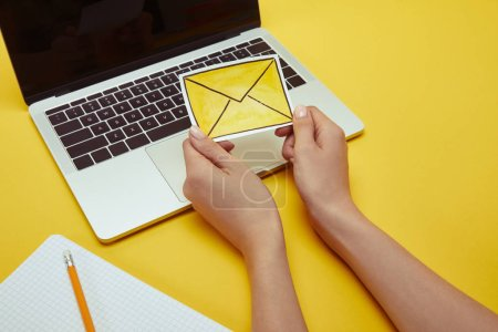 Photo for Cropped image of woman holding envelope sign near laptop - Royalty Free Image