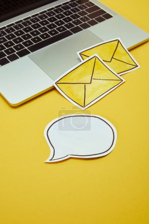 Photo for Message signs, speech bubble and laptop on yellow surface - Royalty Free Image