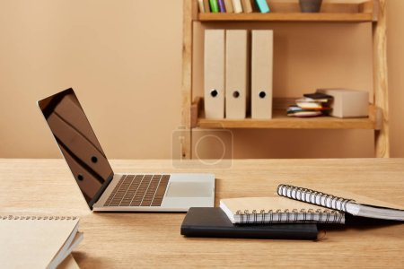 Photo for Laptop and notebooks on wooden table at home - Royalty Free Image