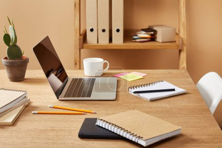 laptop, notebooks and cup of coffee on wooden table at home