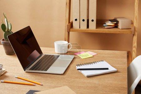 Photo pour Ordinateur portable, cahiers et crayons sur la table en bois à la maison - image libre de droit