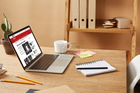Photo for Laptop with loaded bbc news page on wooden table at home - Royalty Free Image