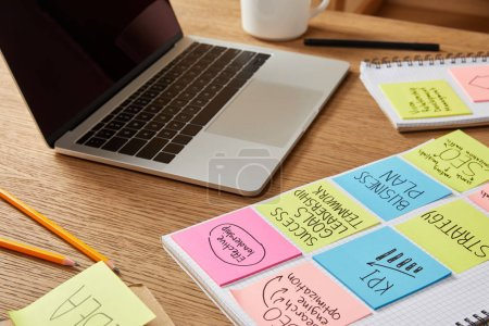 paper stickers with business strategy and laptop on wooden tabletop