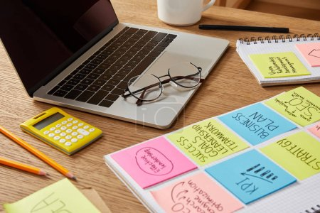 paper stickers with business strategy, calculator and laptop on tabletop