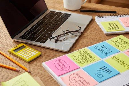 Foto de Etiquetas engomadas de papel con estrategia de negocio, calculadora y ordenador portátil en la mesa - Imagen libre de derechos