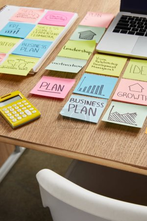 paper stickers with business strategy, calculator and laptop on table