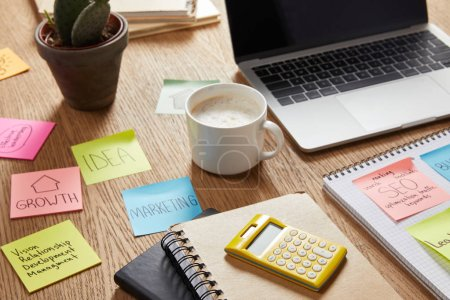 paper stickers with business strategy, cup of coffee and laptop on tabletop