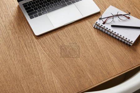 Photo for High angle view of laptop, notebook, glasses and pen on wooden tabletop - Royalty Free Image