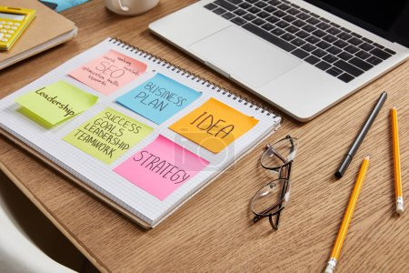 paper stickers with business strategy on notebook and laptop on tabletop