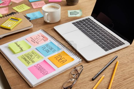 paper stickers with business strategy, glasses and laptop on tabletop