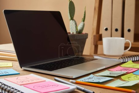 Photo for Laptop with blank screen and paper stickers and cactus on tabletop - Royalty Free Image